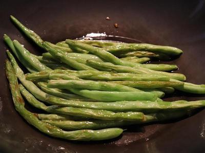 起鍋,油(可多一些),下四季豆,中火,煎炒四季豆,不時用鍋鏟翻一下豆子,以免有一面過熱而焦掉(這就是所謂的「乾煸」),我會「乾煸」到四季豆有點金黃、豆子外觀呈現縮水的感覺(如照片),加鹽1/2小匙,拌炒一下,取出備用。